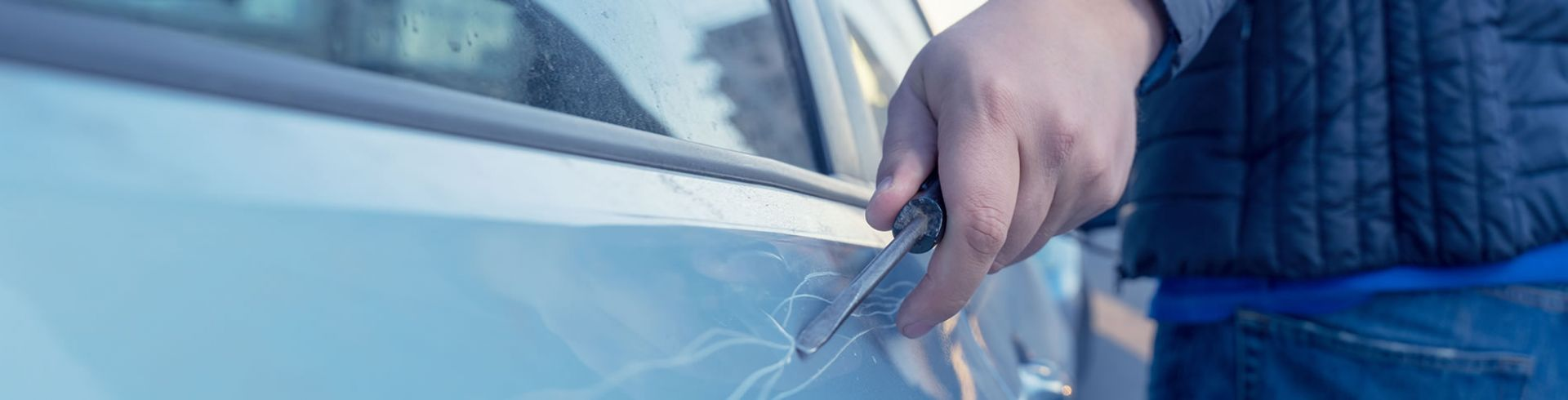 Vandal scratching car with screwdriver